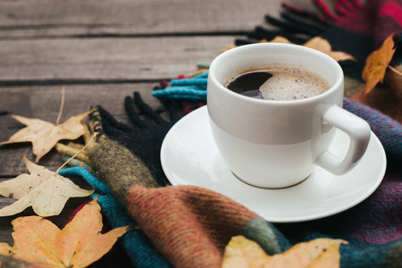Cozy autumn composition with plaid leaves and a cup of coffee on old vintage wooden background. Copy space.