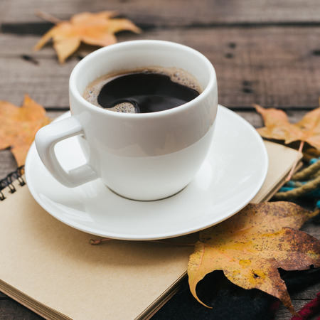 Cozy autumn composition with plaid leaves and a cup of coffee on old vintage wooden background.