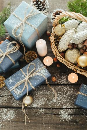 Regalos festivos con cajas, velas, nieve, coníferas, canasta, canela, piñas, nueces sobre fondo de madera. Con espacio para tu texto