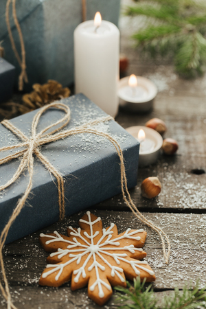 Festive Gifts with Boxes, Candle, Snow, Coniferous, Basket, Cinnamon, Pine Cones, Nuts on Wooden Background.