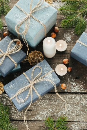 Festive Gifts with Boxes, Candle, Snow, Coniferous, Basket, Cinnamon, Pine Cones, Nuts on Wooden Background. With space for your text