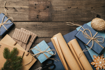 Packing christmas gifts in vintage beige blue roll paper on old wooden desk. Top View. Copy space. Flat Lay.