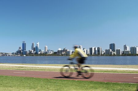 Cyclist riding along a bike path along the edge of the Swan River, with Perth City and the river in the background. Australia Stock Photo