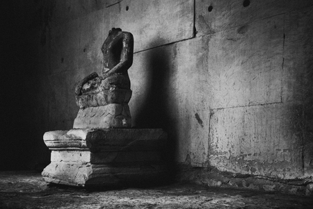 Siem Reap, Cambodia: A headless statue of Buddha in the hallways of Angkor Wat.
