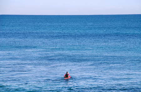 Man paddling a surf ski out into the wide ocean.