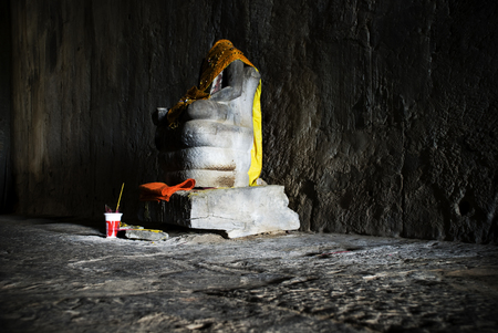 Siem Reap, Cambodia: Headless statue of Buddha in a dark hallway at Angkor Wat. Stock Photo