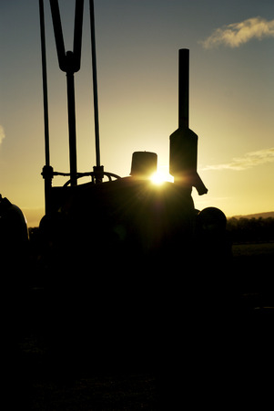 Vintage tractor silhouette at sunset on an Australian farm. Stock Photo
