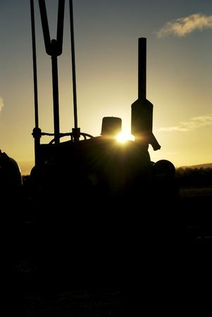 Vintage tractor silhouette at sunset on an Australian farm. Stock Photo