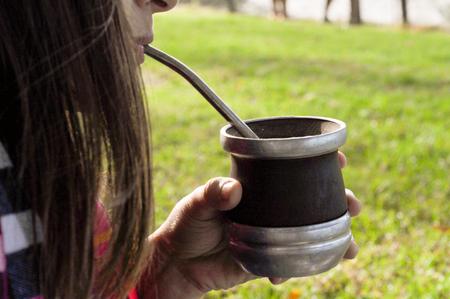 Woman Enjoying Mate drink outdoors Stock Photo