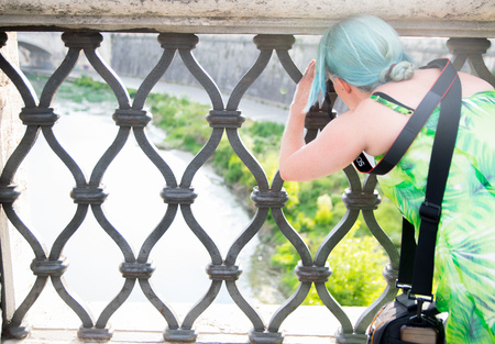 tiber: ROME, ITALY - JUNE 01: A tourist takes a photo of the Vatican City from the railing of Ponte SantAngelo Bridge