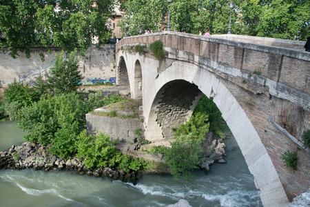 tiber: Ponte Fabricio and Isola Tiberina in Rome, Italy. Fabricius Bridge is the oldest Roman bridge in Rome