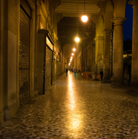 lluminated cobbled street with light reflections on tiling in old historical city by night