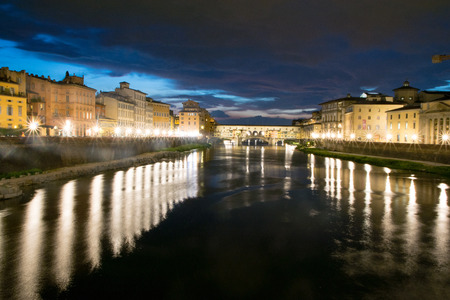View down the Arno River to Ponte Vecchio at night in Florence, Italy