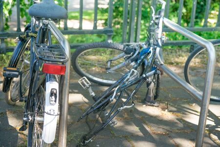discarded: Bike chained to railings with a wheel missing