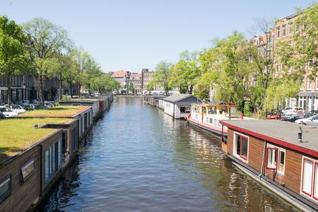 AMSTERDAM, NEDERLAND - 3 juni 2017: Kleurrijke traditionele woonhuizen en woonboten langs het kanaal in Amsterdam, Nederland Stockfoto
