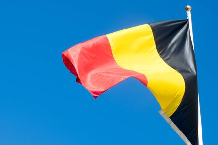 Belgium national flag on flagpole on blue sky background