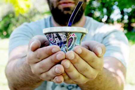 Adult man offering yerba mate drink