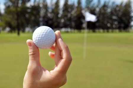 Female hand holding golf ball in a golf course Archivio Fotografico