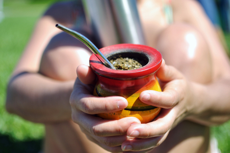 Woman offering yerba mate drink while holds thermo Stock Photo