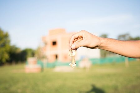 Male hand holding house keys against under construction new home
