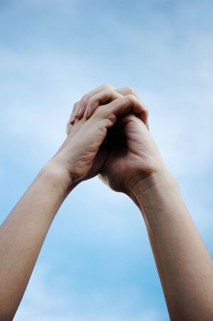 Hands Clasped Against Blue Sky