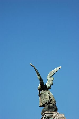 Close View of Angel Statue with wings against blue sky
