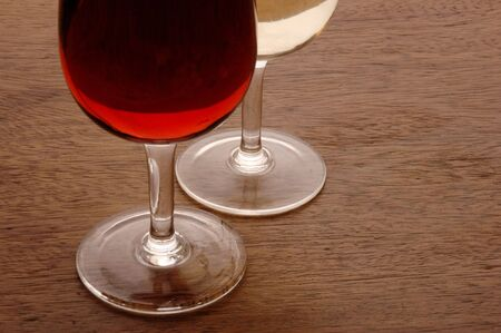 Wine Glasses containing red and white wine on wooden table