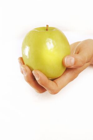 Female hand holding a green apple on white background Stock Photo