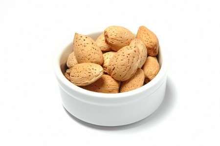 Hazelnuts in bowl against white background