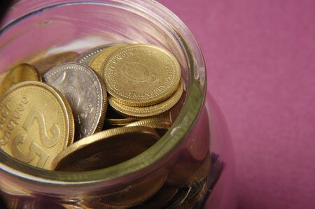 Glass jar with many Coins Banque d'images