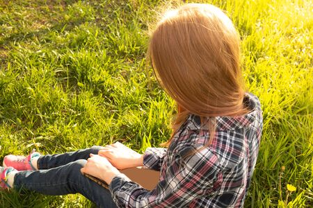 Girl teenager in a plaid shirt with long blond hair reads book outdoor sitting on green grass in park. Selective focus
