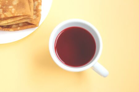 Red hibiscus tea in a white cup with delicious pancakes on a plate isolated on a light orange background. Selective focus. Top view Zdjęcie Seryjne