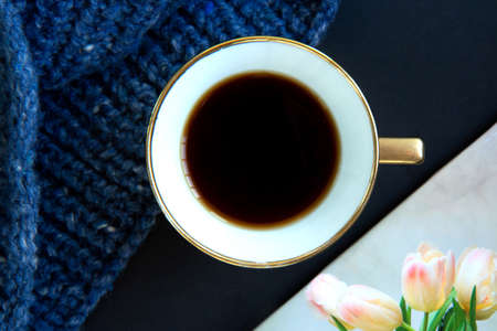 Blue knit sweater, porcelain gold cup with coffee and notepad on black background. Knitwear as a concept of female hobby Stock fotó