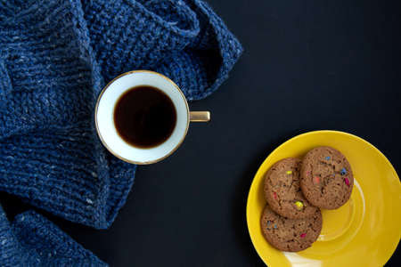 Blue knit sweater, porcelain gold cup with coffee and yellow plate with flavored cookies with colored drops on black background. Craft on black background. Knitwear as a concept of female hobby