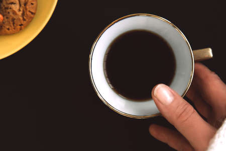Woman's hand is holding a golden porcelain cup of coffee on black background. Yellow plate with flavored cookies with colored drops