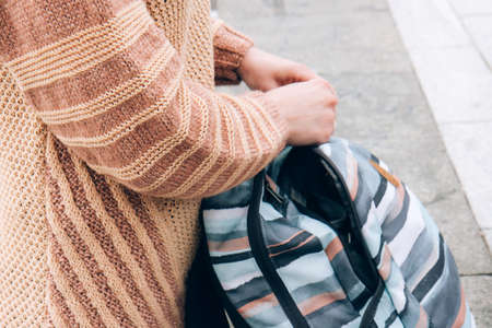 Girl in a cozy beige sweater holds in hands a multi-colored backpack. Autumn soon. To pack