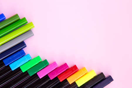 Colorful marker pen set on light pink background. Vivid highlighters and blank space for your design or montage. Background with clipping path. Flat lay