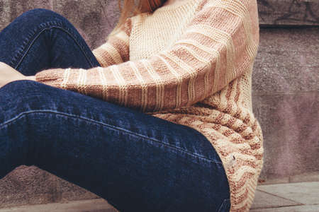 The girl is sitting on the sidewalk. Young beautiful woman in a cozy beige, knitted sweater spends time outdoors. Lifestyle of female