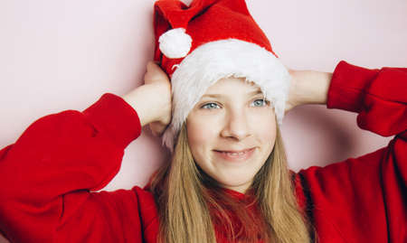 Smiling beautiful girl with long blonde hair in fluffy Santa Claus hat on a pink background. Teenager with bright emotions holding her head with his hands