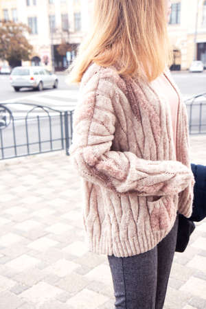 Young beautiful woman in a cozy nude cardigan spends time outdoors. Lifestyle portrait of female. Side view without face