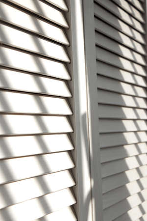Contrasting shadows on classic white louvered doors. Wooden doors