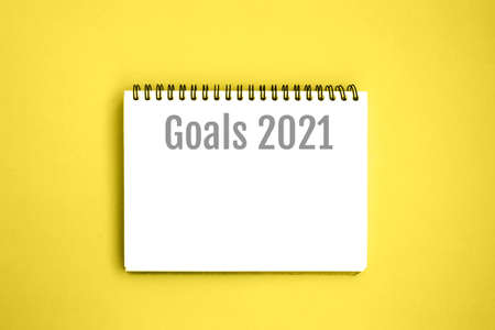 Open notebook with white blank pages on yellow background. Notepad with an inscription: Goals 2021. Stationery on a blue background with space for text. Minimalism. Flat lay