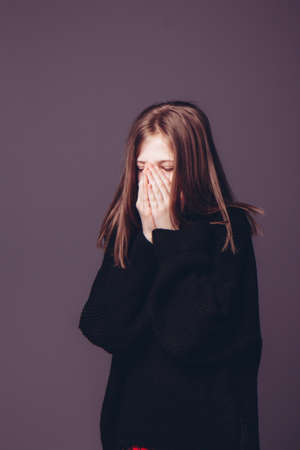 Beautiful girl covered her mouth with her hands on a dark background
