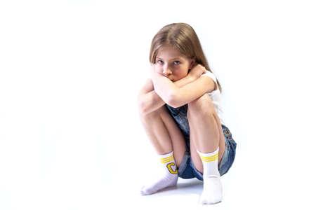 Teenage girl in denim overalls squatting on white background