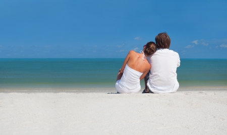 Young couple sitting on the beach looking on the horizon photo