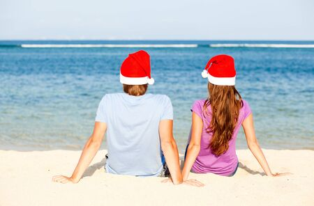 beautiful coulpe in santa hats on tropical beach of Bali photo