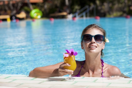 beautiful girl in sunglasses with fresh mango juice in luxury po