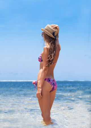back view of young woman in straw and bikini hat standing in sea photo