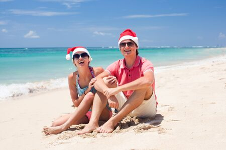 young couple in santa hats laughing on tropical beach  new year photo