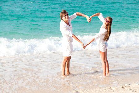 simbolo uomo donna: giovane coppia felice divertirsi in viaggio di nozze spiaggia tropicale